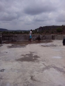 Children's Home roof being washed and prepared for much needed repairs as monsoon clouds loom overhead.